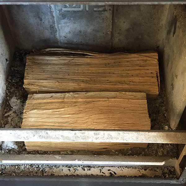 Grote blokken hout onderop om de kachel aan te steken