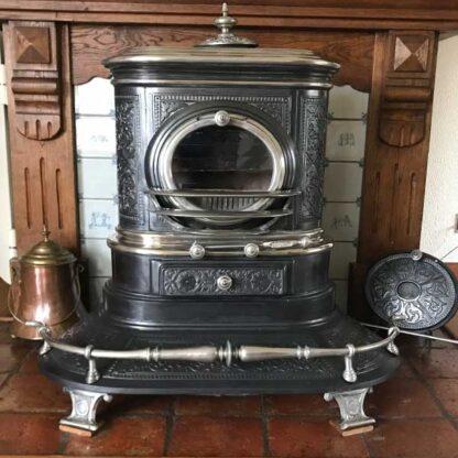 Antieke Friese smits spaarkachel op kolen met voetstoof